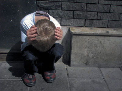 Boy crouching in distress
